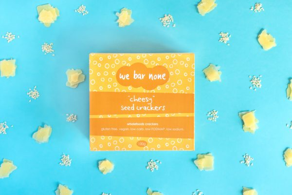 We Bar None Cheesy seed crackers. A box lying on a blue background surrounded by little piles of cheese and sesame seeds.