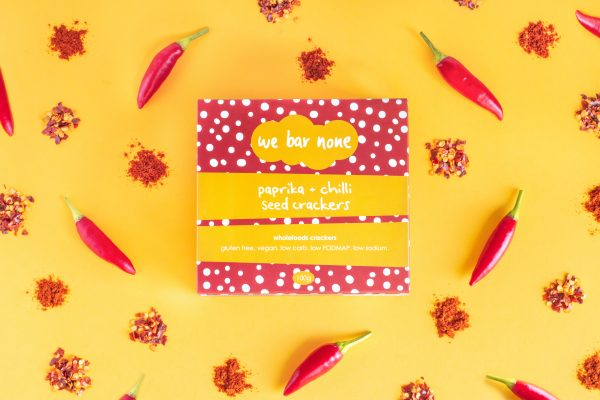 We Bar None Paprika and chilli seed crackers. A box lying on an orange background surrounded by chillis and piles of chilli flakes.