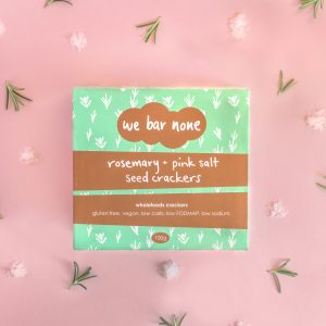 We Bar None Rosemary and pink salt seed crackers. A box lying on a pink background surrounded by little piles of rosemary and salt.